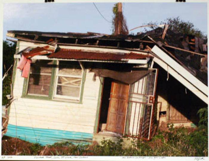 From the series of photographs by Steven L. Smith; image of a destroyed house with green trim around the doors and windows. Steel on the overhang.�� Severe roof damage and foundation damage based no the tilt of the home.